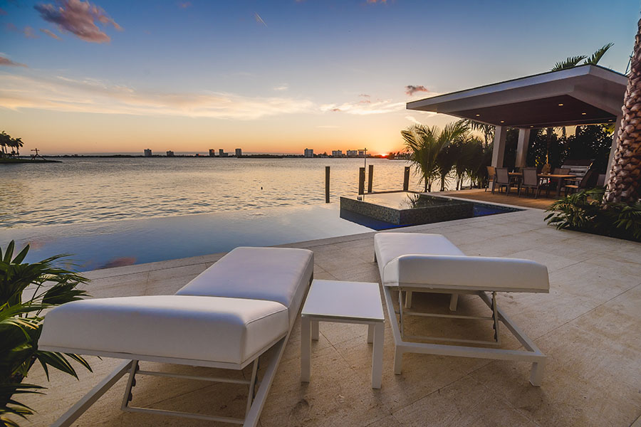 Home Abroad Insurance - View of Lounging Chairs Near the Bay at Sunset